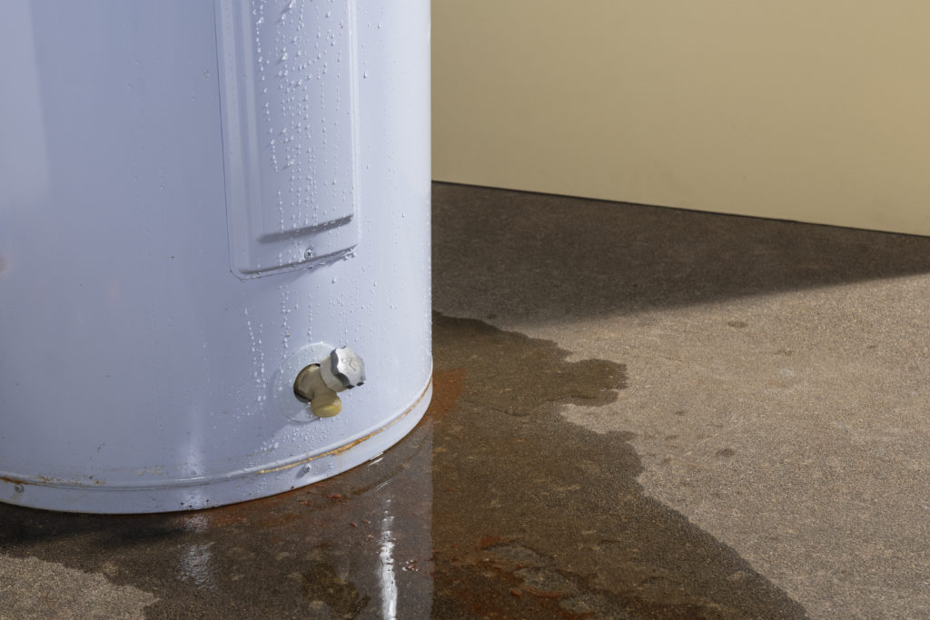 A domestic water heater leaking with signs of rust and iron in the water